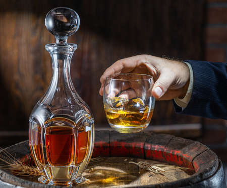 Whiskey tasting. Man sits in front of a barrel with a decanter and a glass of whiskey.
