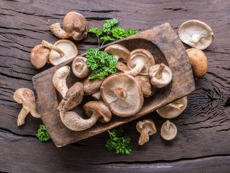 Shiitake edible mushrooms in the wooden plate on wooden table with herbs. Top view.