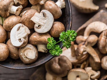 Different brown colored edible mushrooms on wooden table with herbs. Top view.
