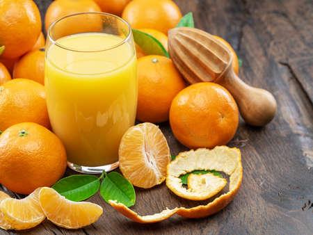 Orange tangerine fruits and glass of fresh tangerine juice
