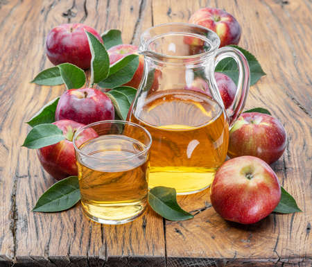 Glass and carafe of fresh apple juice and organic apples on dark old wooden table.