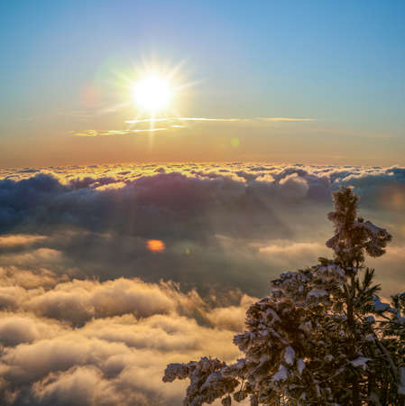 Sunrise shining over the clouds. Beautiful cloudscape and sunrise in thу mountains.