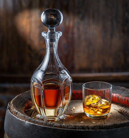 Carafe of whiskey and glass of whiskey on old wooden cask at the dark background.