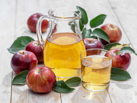 Glass of juice and carafe of fresh apple juice and organic apples on wooden table. Фото со стока