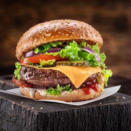 Delicious hamburger on a wooden table with a dark brown background behind. Fast food concept. Фото со стока