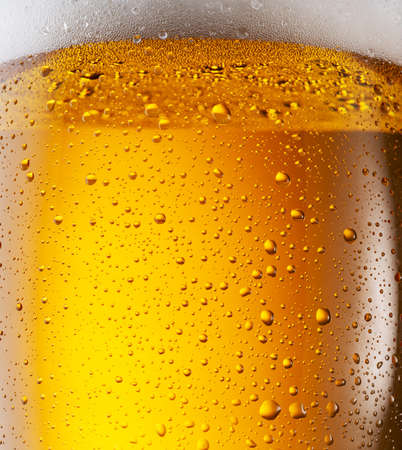 Cooled glass of beer close-up. Small water drops on cold surface of beer glass.