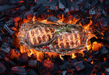 Roasted salmon steaks in aluminum foil on bbq grate over hot pieces of coals. Top view. Фото со стока