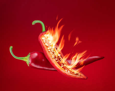 Fresh red chilli pepper in fire as a symbol of burning feeling of spicy food and spices. Red background.