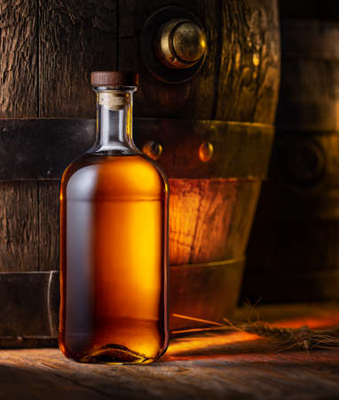 Bottle of whiskey and old wooden cask at the background.