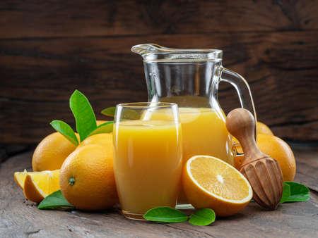 Yellow orange fruits and fresh orange juice isolated on dark wooden background. Фото со стока