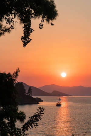 Calm sea and sunset. Sun is setting behind the hills on the horizont. Beautiful nature background.