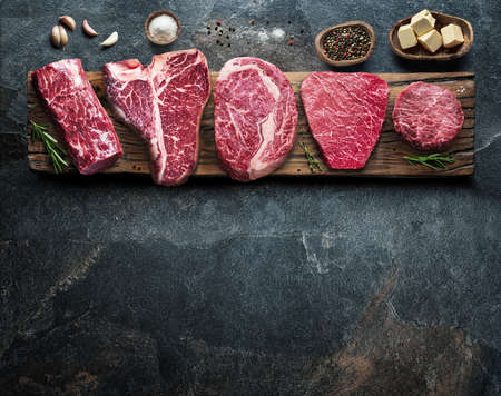 Different raw beef steaks on the wooden board on the gray table. Top view.