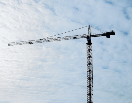 Silhouette of the crane against the sky ahd clouds Stock Photo