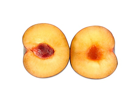 Plum halves on a white background