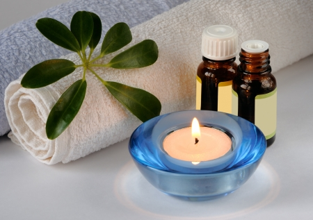 Essential oil bottles, candle and towels