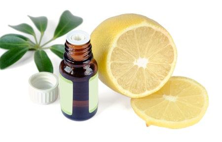 Essential oil bottles and lemon on a white background