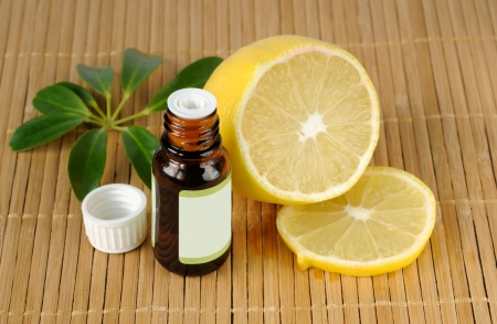 Essential oil bottles and lemon on a mat Stock Photo
