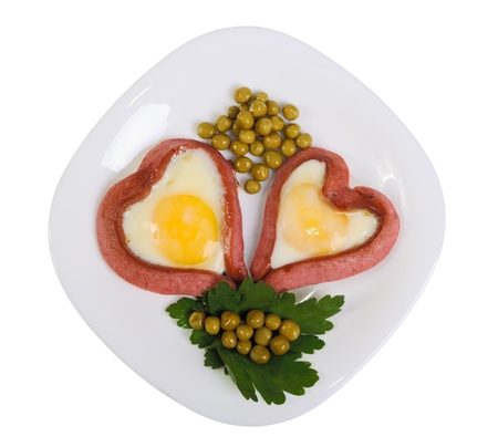 Sausages in the form of two hearts and fried eggs on a white plate isolated on white photo