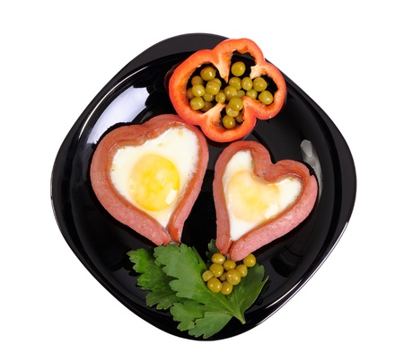 Sausages in the form of two hearts and fried eggs on a black plate isolated on white Stock Photo - 17558489
