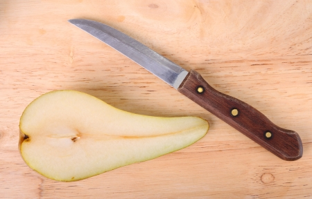 Half of a pear and knife is on a chopping board Stock Photo