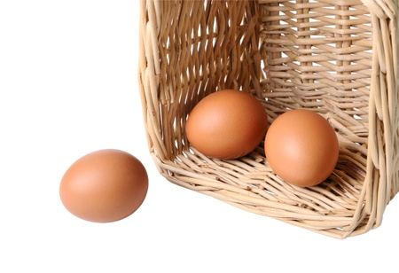 Three eggs in a basket closeup isolated on white photo