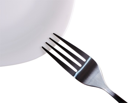 Fork on the edge of a plate closeup Stockfoto