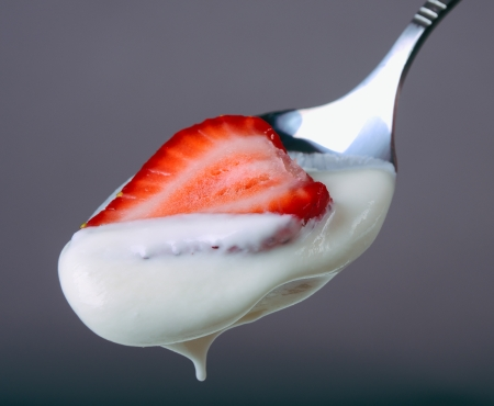 Spoon with strawberry in sour cream closeup