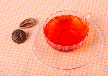Tea in a glass cup, a glass saucer and decoration
