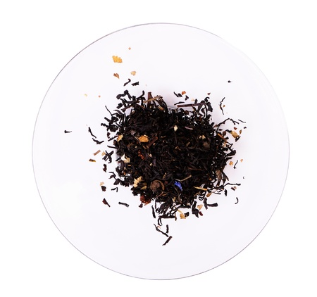 A pile of tea leaves on a glass saucer isolated on white photo