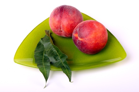 Two peaches with green leaves on a triangular plate on a white background photo