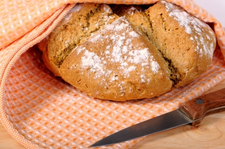 dishcloth: Newly-baked bread in a dishcloth and a knife