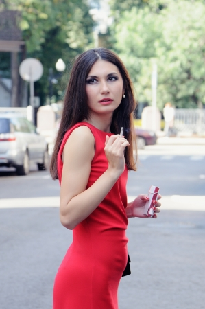 Girl with a cigarette in one arm and a cigarette pack in other turns around back photo