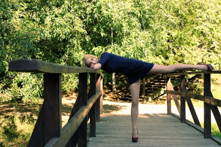 fooling: Girl fooling around on a wooden bridge Stock Photo