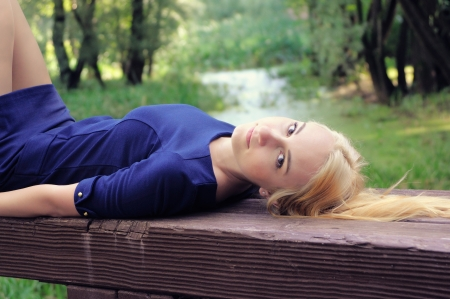 The girl the blonde lies on a wooden bench of park