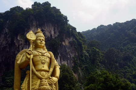 god figure: Kuala Lumpur, Malaysia - November 3, 2014:  42-meter statue of Lord Murugan that stands next to the stairs, leading to the top Batu Caves, located in Malaysia