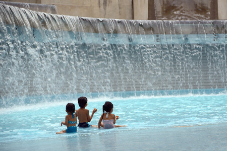 Kuala Lumpur, Malaysia - November 5, 2014: Children playing in a man-made waterfall in the KLCC Park in Kuala Lumpur, Malaysia. This city park was designed by Brazilian architect Roberto Burle Marx.