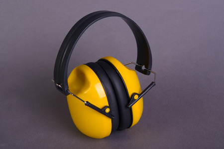 Yellow ear muffs on gray  background