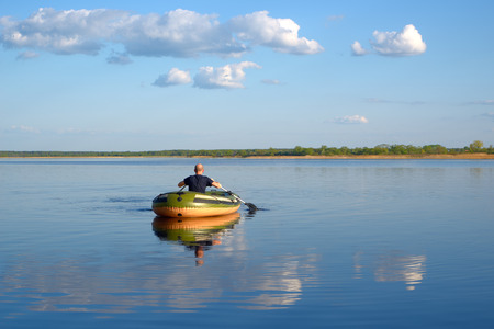 Man in an inflatable boat floats on the river, the view from the back