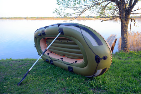inflatable boat: Inflatable boat dries leaning on an oar, on the river bank Stock Photo
