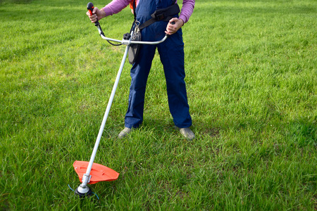 mowing grass: Man mowing grass with petrol weed trimmer