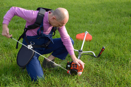 The man starts a weed trimmer on a lawn Stock Photo
