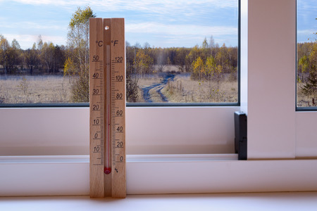 sunny cold days: Thermometer on the plastic window and sunny autumn landscape in the background