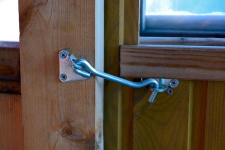 hook up: Metal hook on wooden door close up