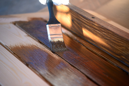 staining: Hand with a brush paints a wooden surface with brown paint, close up