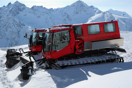 Two snowcat standing high in the mountains