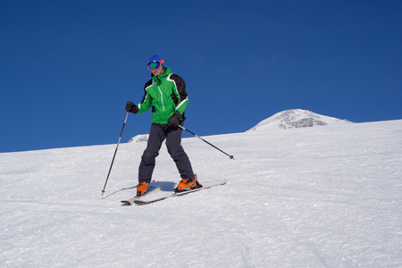 Skier going down the snowy slope Stock Photo