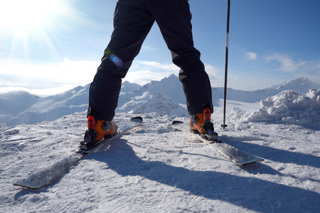 Close up of ski legs and ski pole against mountain background, low angle