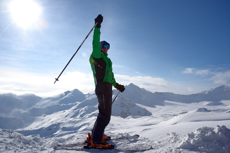 Skier on the top of ski slope with a raised hand in a joyful gesture