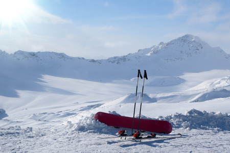 Snowboard and skis in the snow on background snowy mountains Stock Photo