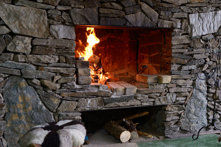 Close up of stone fireplace with burning logs Stock Photo
